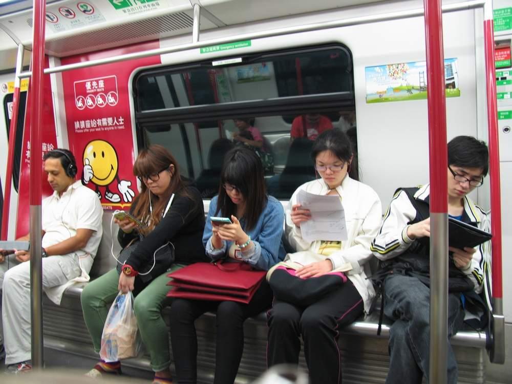 пассажиры в вагоне метро с гаджетами