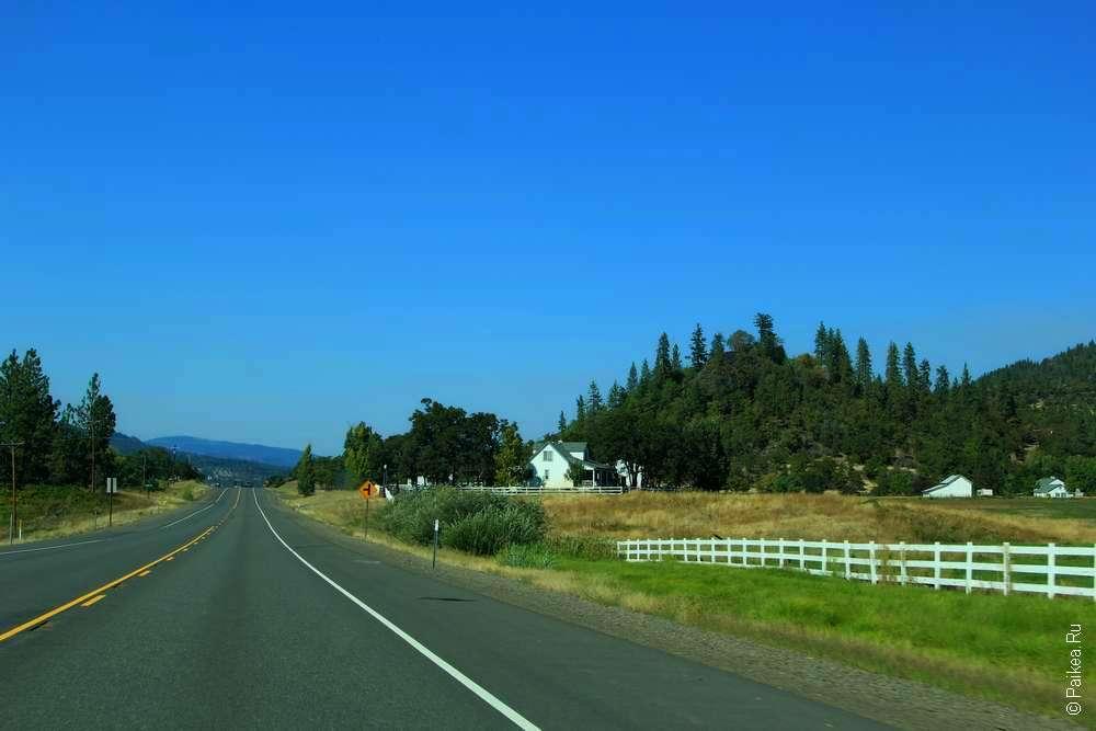 Белый забор и дом у дороги