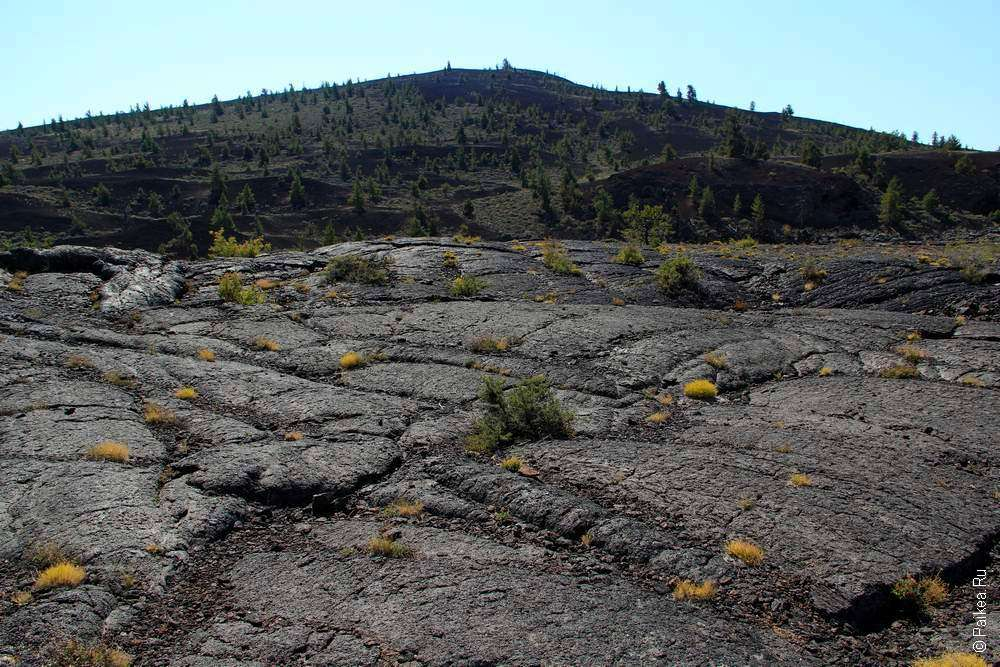 Поле из лавы на фоне лунного кратера