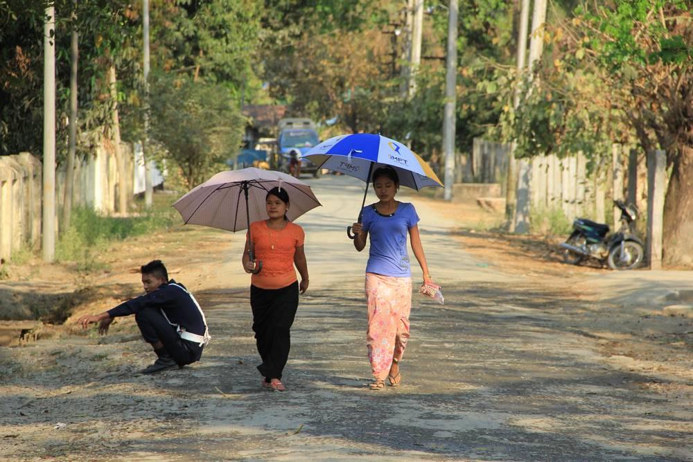 Идут под зонтиками по деревне в Мьянме
