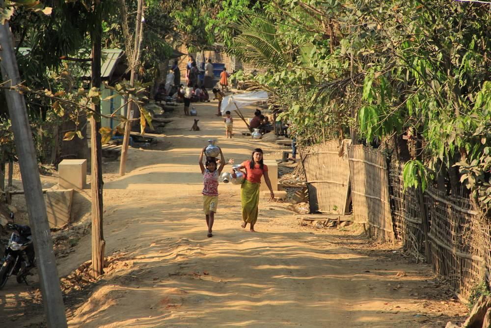 Несут кувшины с водой по деревне в Мьянме