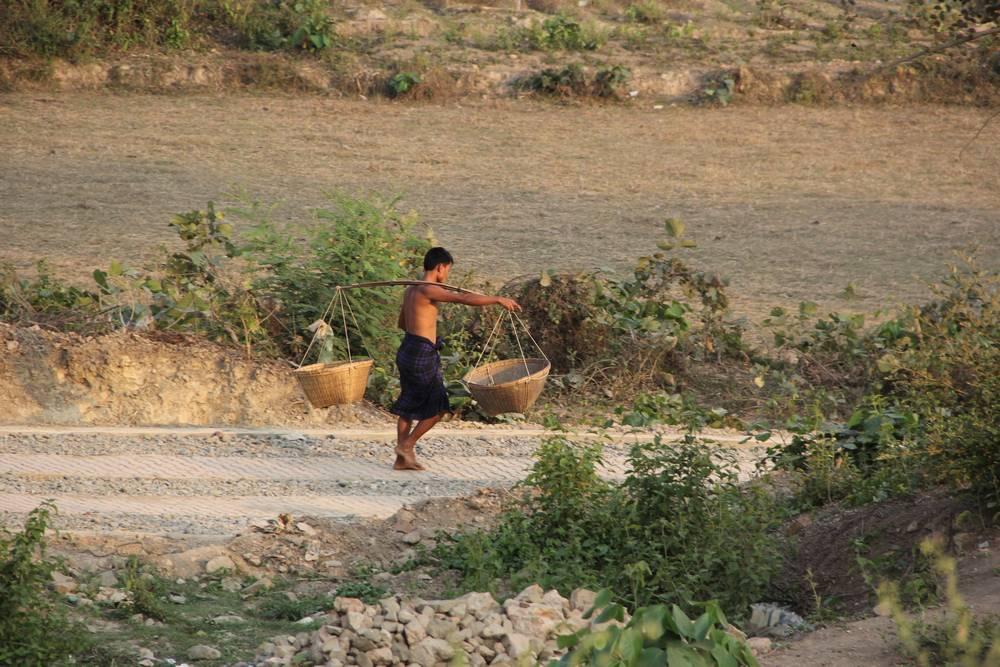 Мужчина с коромыслом в Мьянме